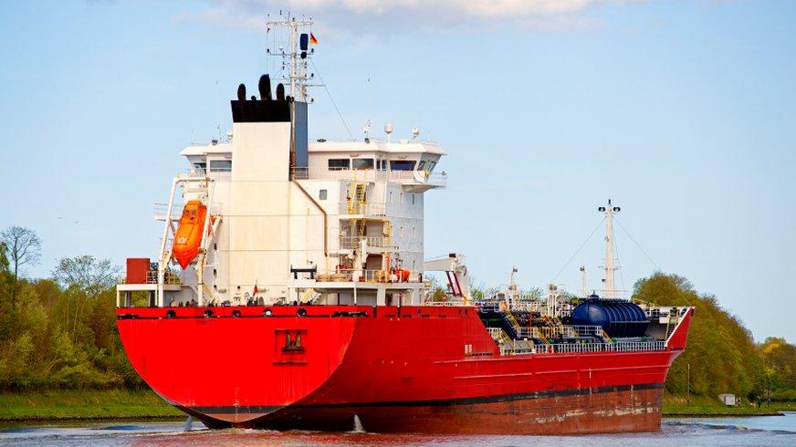 rotes Frachtschiff in Fahrt auf einem Fluss